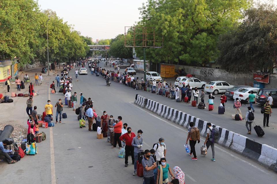 People wait in long queues at a railway station to board trains back to their home states during the covid 19 pandemic. India announces a limited reopening of its giant rail network following a nearly seven-week lockdown to slow the spreading of the coronavirus disease (COVID-19). (Photo by Amarjeet Kumar Singh/SOPA Images/LightRocket via Getty Images)