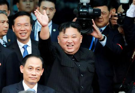 North Korean leader Kim Jong Un bids farewell to the crowd before boarding his train to depart for North Korea at Dong Dang railway station