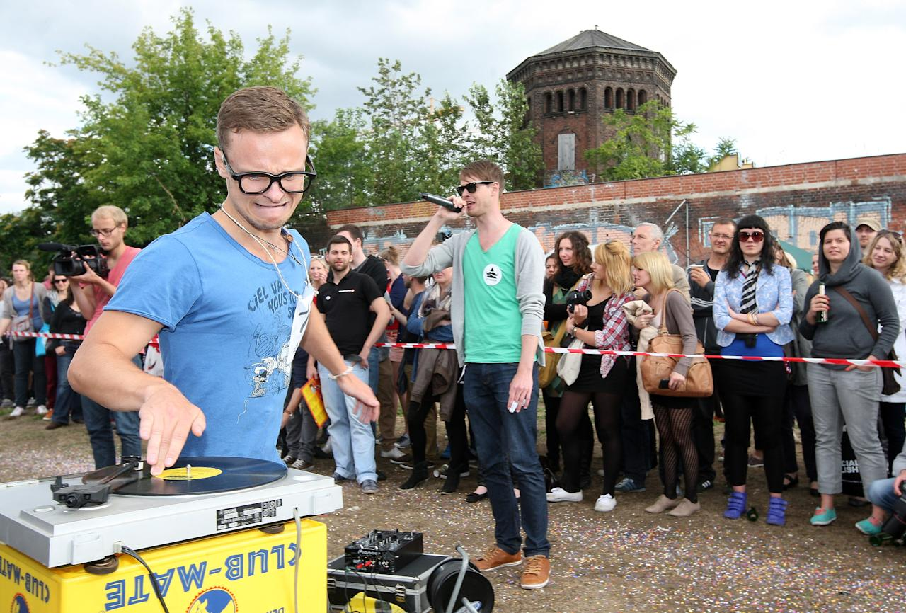 "BERLIN, GERMANY - JULY 21:  A contestant competes in the ""Vinyl Record Spinning Contest,"" in which competitors must run around a record player while keeping a finger on a record, at the second annual Hipster Olympics on July 21, 2012 in Berlin, Germany. With events such as the ""Horn-Rimmed Glasses Throw,"" ""Skinny Jeans Tug-O-War,"" ""Vinyl Record Spinning Contest"" and ""Cloth Tote Sack Race,"" the Hipster Olympics both mocks and celebrates the Hipster subculture, which some critics claim could never be accurately defined and others that it never existed in the first place. The imprecise nature of determining what makes one a member means that the symptomatic elements of adherants to the group vary in each country, but the archetype of the version in Berlin, one of the more popular locations for those following its lifestyle, along with London and Brooklyn, includes a penchant for canvas tote bags, the carbonated yerba mate drink Club Mate, analogue film cameras, asymmetrical haircuts, 80s neon fashion, and, allegedly, a heavy dose of irony. To some in Berlin, members of the hipster ""movement"" have replaced a former unwanted identity in gentrifying neighborhoods, the Yuppie, for targets of criticism, as landlords raise rents in the areas to which they relocate, particularly the up-and-coming neighborhood of Neukoelln.  (Photo by Adam Berry/Getty Images)"