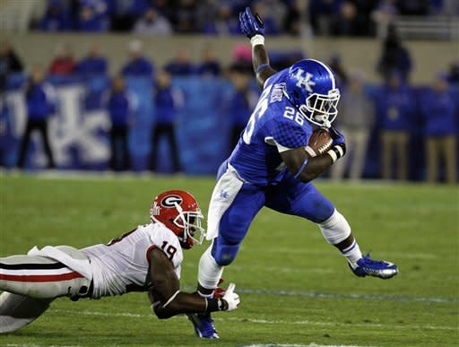 Kentucky tailback Raymond Sanders (26) tries to get away from Georgia cornerback Sanders Commings (19) on a first half run during their NCAA college football game in Lexington, Ky., Saturday, Oct. 20, 2012. (AP Photo/Garry Jones)