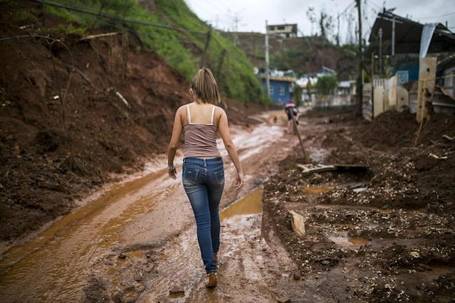 <p>A resident walks along a muddy road in Barranquitas, Puerto Rico, on Wednesday, Oct. 18, 2017. (Photo: Xavier Garcia/Bloomberg via Getty Images) </p>