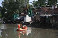 National Disaster Response Force personnel inspect on a dinghy the area where some shanty houses collapsed into a canal due to heavy rains in New Delhi on July 19, 2020. (Photo by Sajjad HUSSAIN / AFP) (Photo by SAJJAD HUSSAIN/AFP via Getty Images)