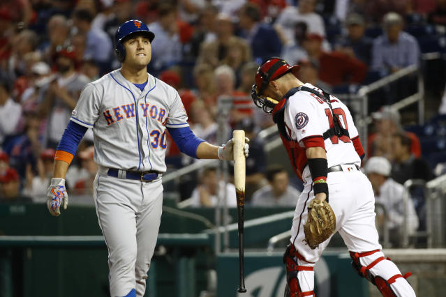 New York Mets' Michael Conforto, left, walks off the field past Washington Nationals catcher Yan Gomes after striking out swinging in the fourth inning of a baseball game, Wednesday, May 15, 2019, in Washington. Washington won 5-1. (AP Photo/Patrick Semansky)