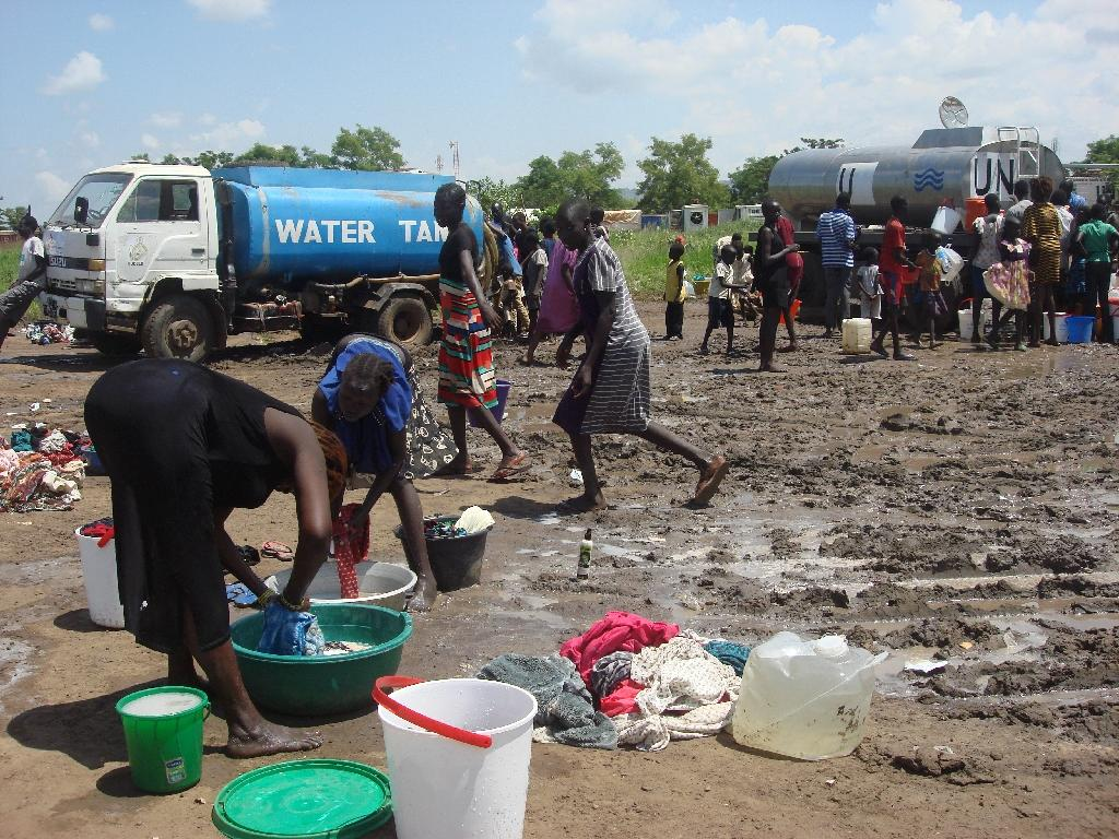 This handout photo provided by the United Nations Mission in the Republic of South Sudan (UNMISS) and released on July 16, 2016 shows women doing laundry as people collect water at the UN compound in the Tomping area in Juba (AFP Photo/Beatrice Mategwa)