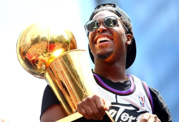 In this June 2019 file photo, Kyle Lowry holds the championship trophy during the Toronto Raptors victory parade in Toronto, Canada. Lowry and the Raptors beat the Golden State Warriors 4-2 to win the 2019 NBA Finals. (File/Getty Images - image credit)