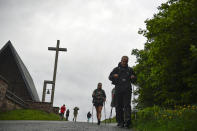 Pilgrims of St. James Way walk at the area of Ibaneta mountain, near to Roncesvalles, northern Spain, Tuesday, June 1, 2021. The pilgrims are trickling back to Spain's St. James Way after a year of being kept off the trail due to the pandemic. Many have committed to putting their lives on hold for days or weeks to walk to the medieval cathedral in Santiago de Compostela in hopes of healing wounds caused by the coronavirus. (AP Photo/Alvaro Barrientos)