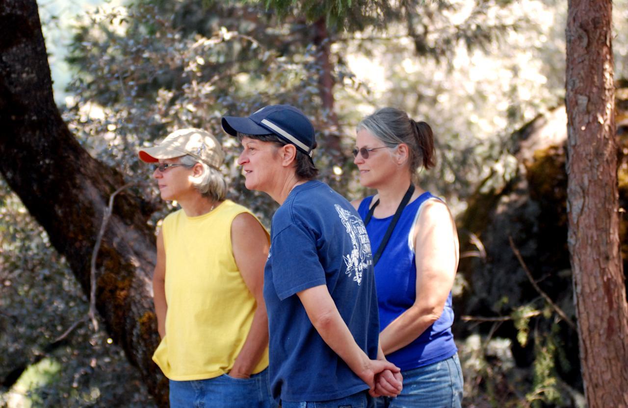 From left, Kelly Strong, Jane Carney and Sherrill Jenkins, owners of a vacation home in the community of Mineral, Calif., watch helicopters drop water and fire retardant on the Ponderosa Fire. The women said they have gathered belongings from the vacation house and stacked them downstairs in case they get the order to evacuate. The Ponderosa Fire is 57 percent contained, with full containment expected early next week. (AP Photo/Jeff Barnard)