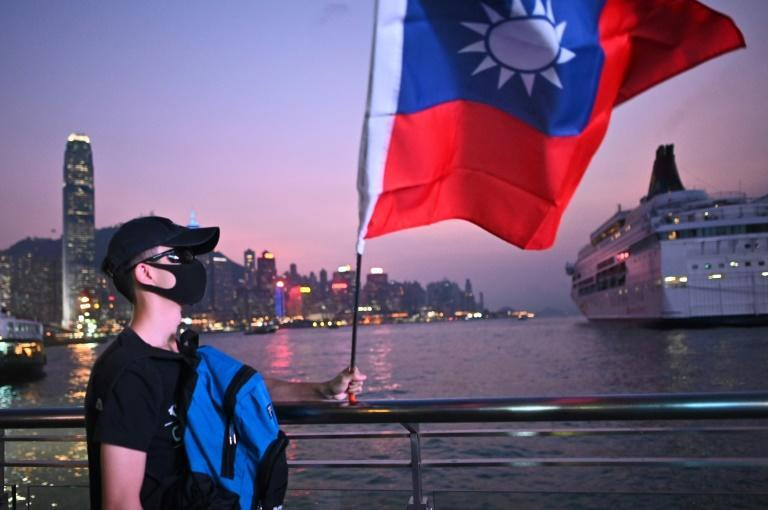 A masked man holds a Taiwanese flag at a 'Double Tenth' rally in 2019 (AFP/Philip FONG)