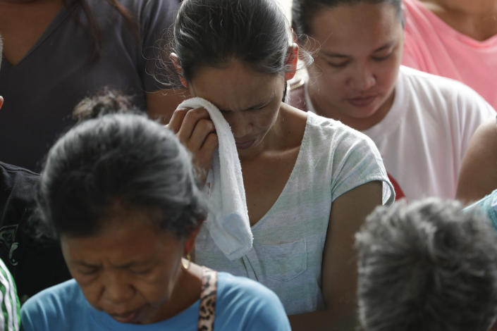 A woman wipes a tear during prayers before the distribution of relief goods at an evacuation center at Santa Teresita, Batangas province, southern Philippines on Thursday Jan. 16, 2020. Taal volcano belched smaller plumes of ash Thursday but shuddered continuously with earthquakes and cracked roads in nearby towns, which were blockaded by police due to fears of a bigger eruption. (AP Photo/Aaron Favila)