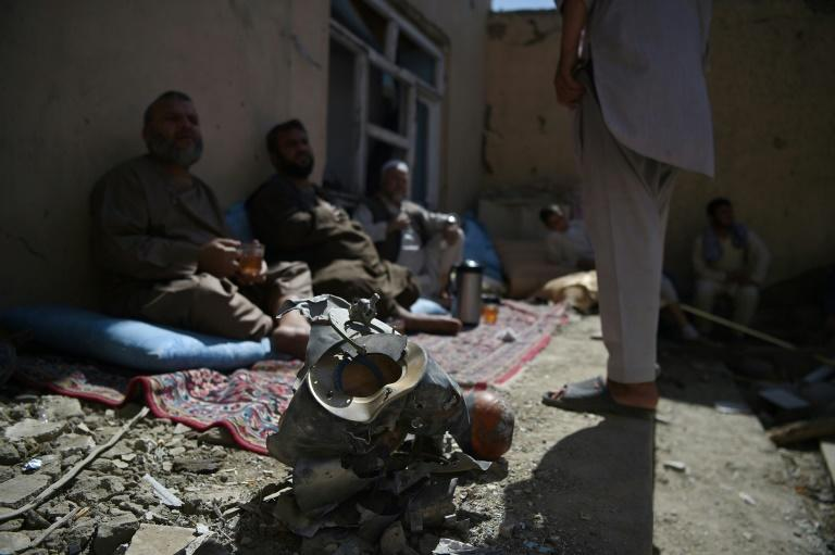 Afghan residents drink tea in a damage courtyard following a hit by a NATO airstrike at a residential house in Kabul on September 28, 2017