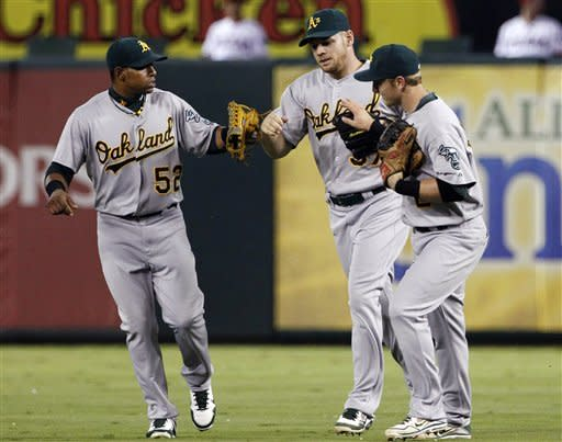 Oakland Athletics' Yoenis Cespedes (52) and Cliff Pennington, right, congratulate right fielder Brandon Moss, center, on his catch against the wall on a bases-loaded fly ball from Texas Rangers' Elvis Andrus in the seventh inning of a baseball game, Tuesday, Sept. 25, 2012, in Arlington, Texas. The Athletics won 3-2 in the 10th inning. (AP Photo/Tony Gutierrez)