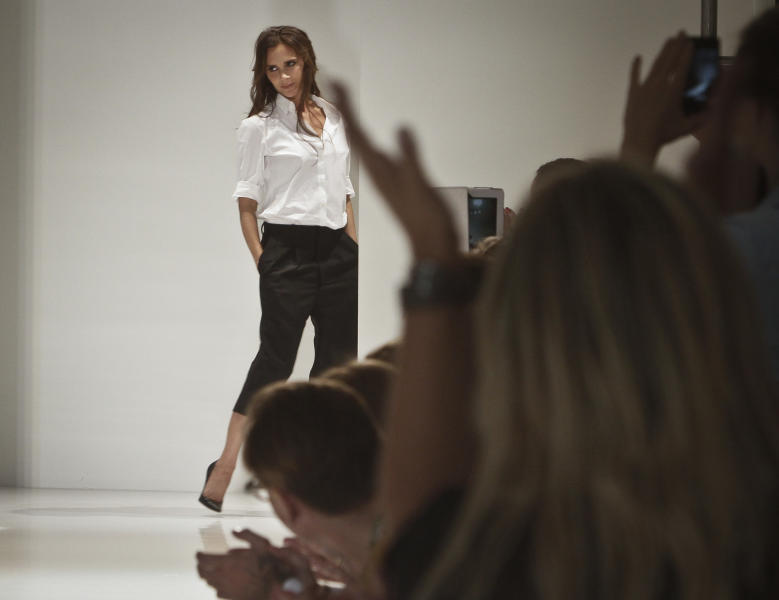 Victoria Beckham reacts to applause following the runway fashion show of her Spring 2014 collection on Sunday, Sept. 8, 2013 in New York. (AP Photo/Bebeto Matthews)