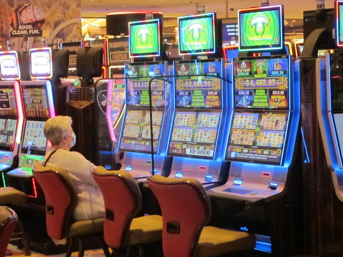 In this May 3, 2021 photo a woman plays a slot machine while wearing a mask in the Hard Rock casino in Atlantic City, N.J. On May 11 the American Gaming Association released statistics showing that the U.S. commercial casino industry matched its best quarter ever in terms of revenue in the first three months of 2021, taking in more than $11.1 billion as customers continued returning amid the COVID-19 pandemic. (AP Photo/Wayne Parry)