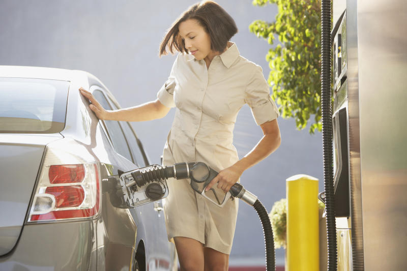 A woman pumping gas at a gas station.