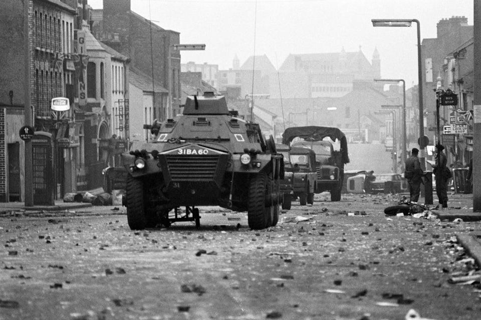 Armoured cars rumble over the rubble past overturned cars and a wrecked motor cycle at dawn in Belfast's Protestant Shankill Road, after a night of violence in which three people died. (PA Archive)