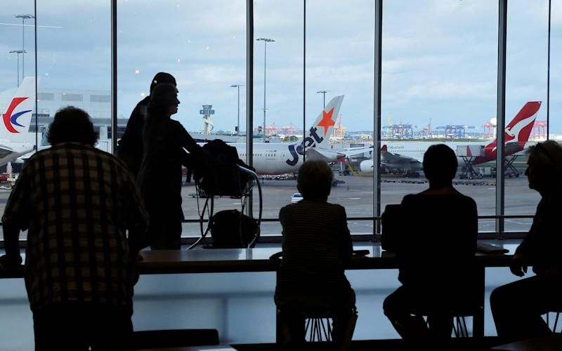 Passengers wait to board their flights at the Sydney International Airport - Credit: Reuters