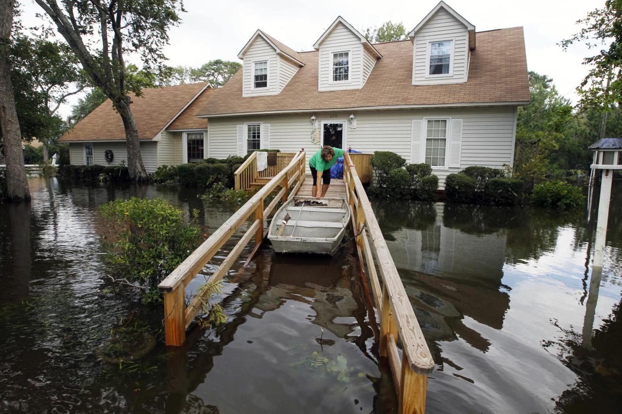 Lechelle Spalding pulls a boat up to her flooded home after a storm surge on the Outer Banks in Kitty Hawk, N.C., Sunday, Aug. 28, 2011 in the aftermath of Hurricane Irene after it left the North Carolina coast. (AP Photo/Charles Dharapak)