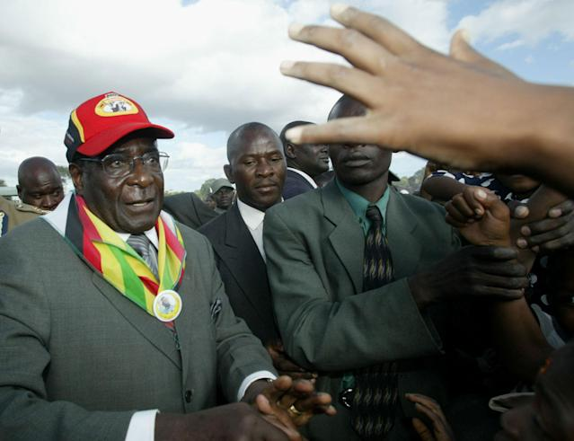 <p>Mugabe greets the crowd upon arrival at a rally in Gutu, Zimbabwe, in 2005. (Photo: AP) </p>