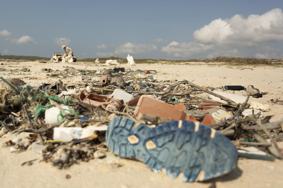 A shoe and other household items strewn across the sand. A figure in the background picks up trash.