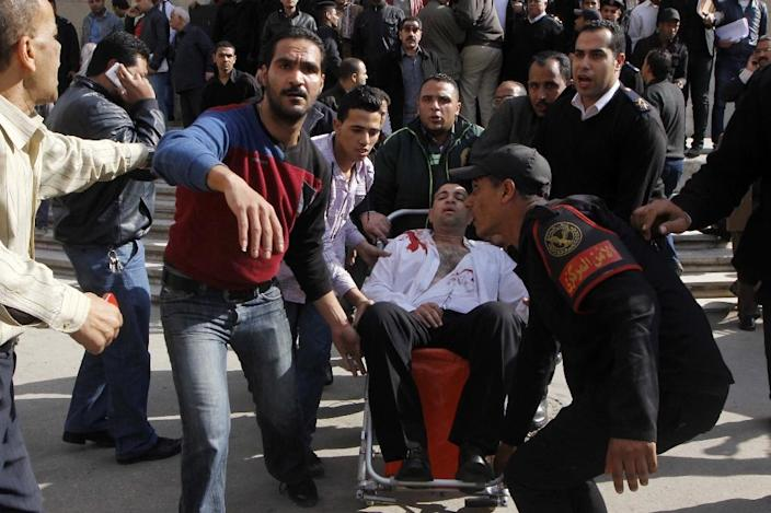 Egyptians help an injured man following an explosion outside the Supreme Court in Cairo, on March 2, 2015 (AFP Photo/)
