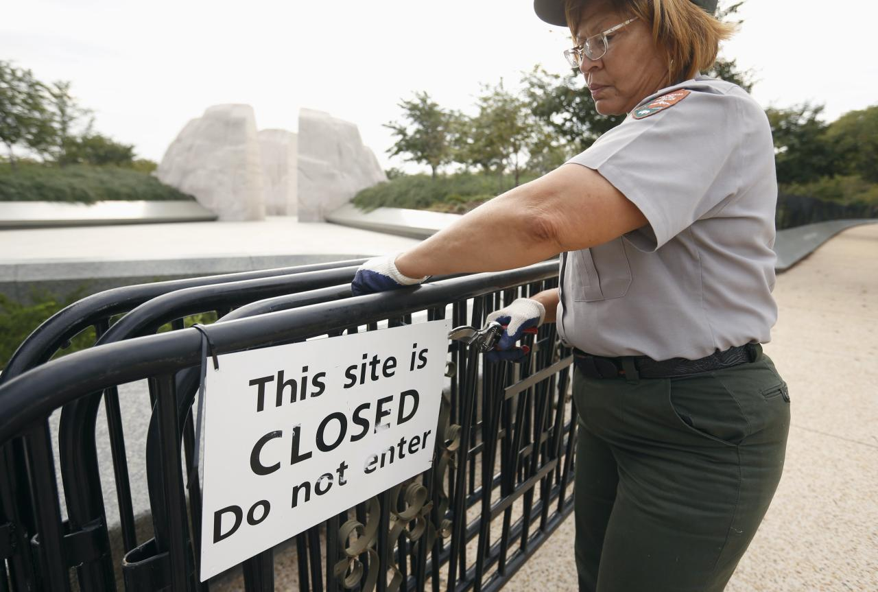 A National Park worker removes a closed sign at the Martin Luther King Jr. Memorial after it was re-opened to the public in Washington October 17, 2013. The White House moved quickly early on Thursday to get the U.S. government back up and running after a 16-day shutdown, directing hundreds of thousands of workers to return to work. REUTERS/Kevin Lamarque (UNITED STATES - Tags: POLITICS BUSINESS EMPLOYMENT SOCIETY)