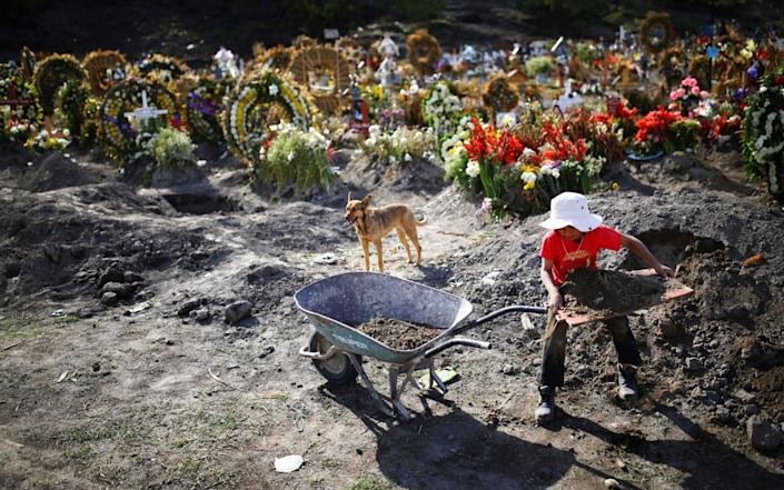 Jesus, a boy who works with his father cleaning and decorating graves, loads land on a wheelbarrow at the Xico cemetery on the outskirts of Mexico City - Reuters