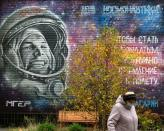 A woman walks past a mural depicting cosmonaut Yuri Gagarin in Star City near Moscow