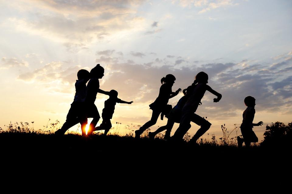 Kids running in a field at sunset
