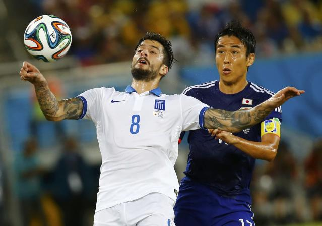 Greece's Panagiotis Kone (L) fights for the ball with Japan's Makoto Hasebe during their 2014 World Cup Group C soccer match at the Dunas arena in Natal June 19, 2014. REUTERS/Kai Pfaffenbach (BRAZIL - Tags: SOCCER SPORT WORLD CUP)
