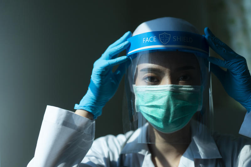 Closeup Asian female Doctor wearing face shield and PPE suit and praying for stop Coronavirus outbreak or Covid-19, Concept of Covid-19 quarantine