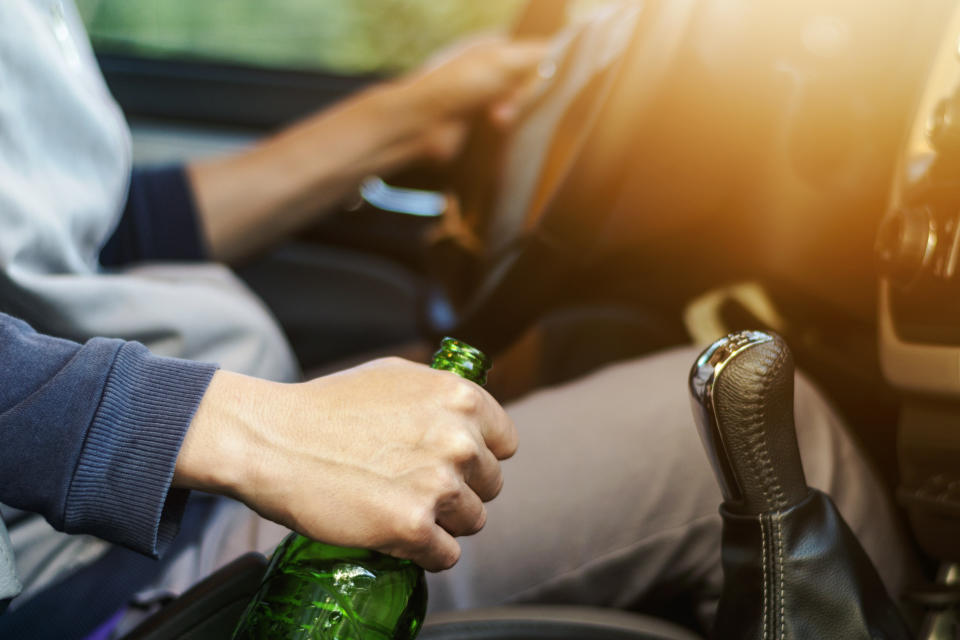 Drinking and driving ,man drinking alcohol and using mobile phone while driving car ,concept drive safely while using a cell phone or drunk alcohol.