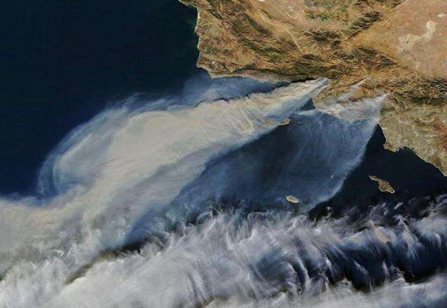 <p>Thick smoke streams from several fires in southern California on Dec. 5, 2017. The largest of the blazes – the fast-moving Thomas fire in Ventura County – had charred more than 65,000 acres, according to Cal Fire. Smaller smoke plumes from the Creek and Rye fires are also visible. (Photo: NASA/AFP) </p>