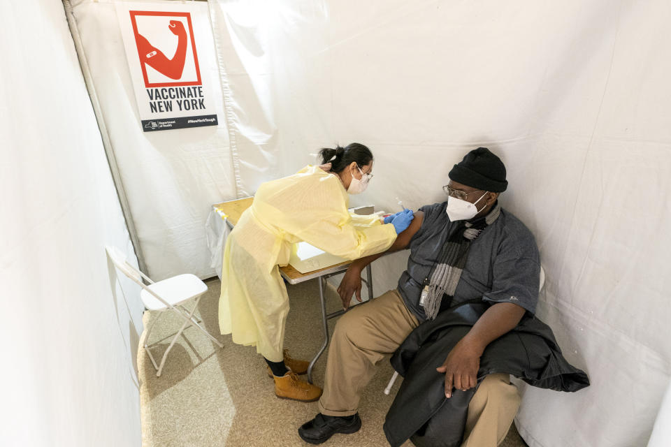 FILE - In this Jan. 23, 2021, file photo, registered Nurse Shyun Lin, left, gives Roberto Fisher, 72, the first dose of the COVID-19 vaccine at a pop-up vaccination site in the William Reid Apartments in the Brooklyn borough of New York. Coronavirus deaths and cases per day in the U.S. dropped markedly over the past couple of weeks but are still running at alarmingly high levels, and the effort to snuff out COVID-19 is becoming an ever more urgent race between the vaccine and the mutating virus. (AP Photo/Mary Altaffer, Pool, File)