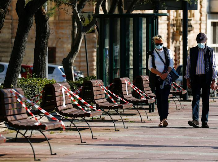 FILE PHOTO: A man and a woman wearing protective face masks walk past benches that have been taped off to prevent people from sitting on them, as people take advantage of the good weather to go outdoors in Sliema, despite the outbreak of the coronavirus disease (COVID-19) in Malta April 12, 2020. REUTERS/Darrin Zammit Lupi