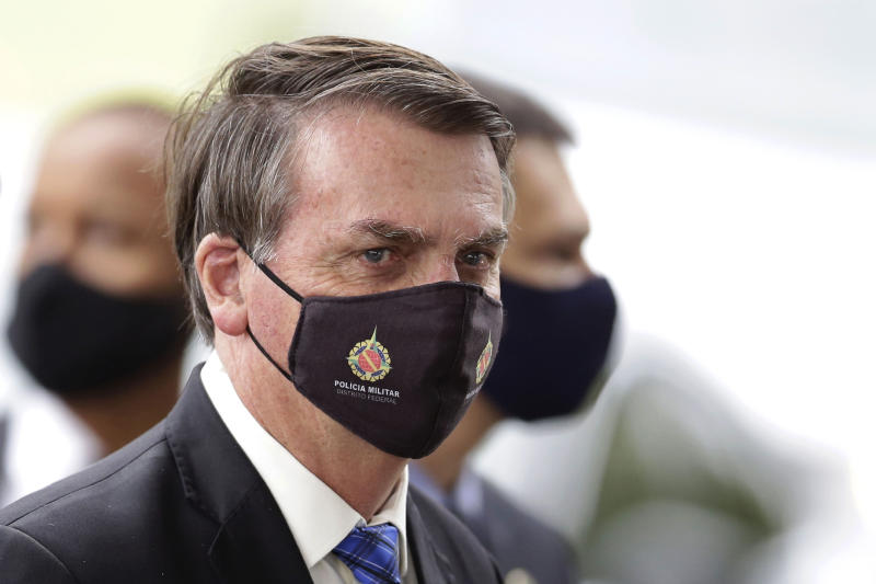 "Brazilian President Jair Bolsonaro wears a mask due to the COVID-19 pandemic as he talks with supporters upon departure from his official residence, Alvorada palace, in Brasilia, Brazil, Monday, May 18, 2020. The logo on the mask reads ""Military Police. Federal District."" (AP Photo/Eraldo Peres)"