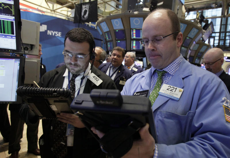 In this May 11, 2012, photo, trader Peter Mancuso, right, works on the floor of the New York Stock Exchange.  U.S. stocks were set for a moderately higher opening Thursday May 17, 2012, with Dow Jones industrial futures up 0.3 percentand S&P 500 futures up 0.4 percent.   (AP Photo/Richard Drew)