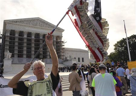 David Barrows (L) waves a self-made U.S. flag covered in fake currency and corporate logos during a protest in front of the U.S. Supreme Court in Washington October 8, 2013. REUTERS/Gary Cameron