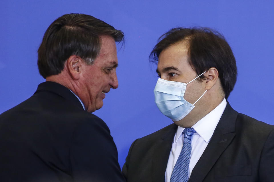Brazilian President Jair Bolsonaro walks past the President of the Chamber of Deputies Rodrigo Maia during an official ceremony at the presidential office in Brasilia on June 17, 2020. (Photo by Sergio LIMA / AFP) (Photo by SERGIO LIMA/AFP via Getty Images)