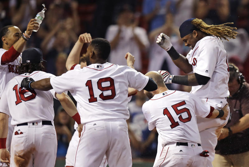 Boston Red Sox's Hanley Ramirez, right, is welcomed by teammates after his game-winning solo home run during the 15th inning of the team's baseball game against the Toronto Blue Jays at Fenway Park in Boston, early Wednesday, July 19, 2017. The Red Sox won 5-4. (AP Photo/Charles Krupa)