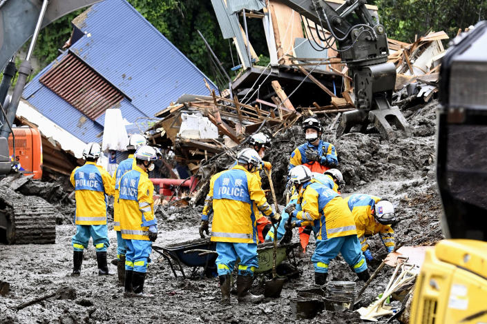 Rescuers work to clear mud at the site of a mudslide in Atami, southwest of Tokyo Wednesday, July 7, 2021. Workers are searching carefully inside homes that were destroyed and filled with mud in Saturday's disaster. (Kyodo News via AP)