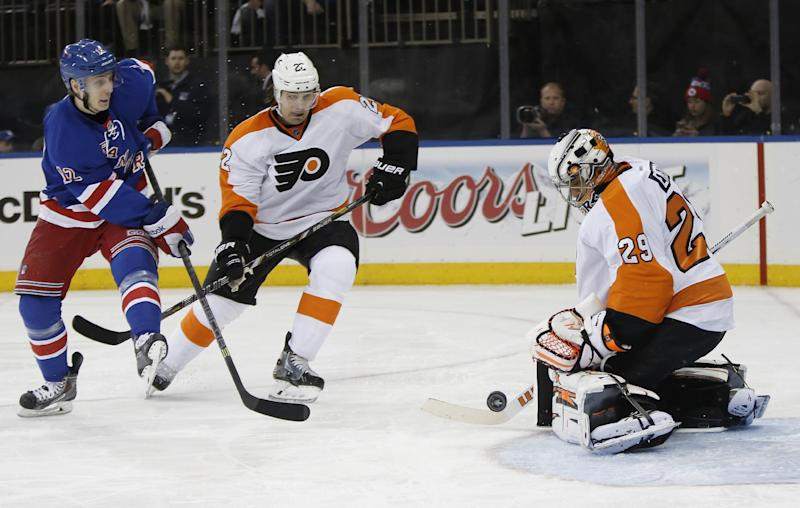 Philadelphia Flyers goalie Ray Emery (29) blocks a shot by New York Rangers right wing Jesper Fast (12), of Sweden, with Flyers defenseman Luke Schenn (22) defending, in the second period of Game 2 of the first round of the Stanley Cup hockey playoffs at Madison Square Garden in New York , Sunday, April 20, 2014. (AP Photo/Kathy Willens)