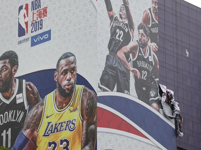 A worker taking down the Lakers-Nets promotional poster.