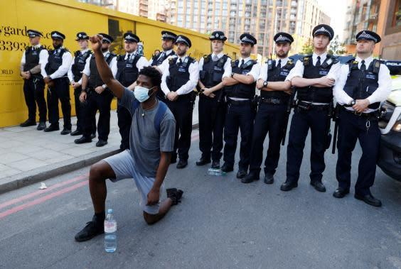 A man wearing a protective face mask kneels in front of police officers during a protest against George Floyd's death near the US embassy (Reuters)