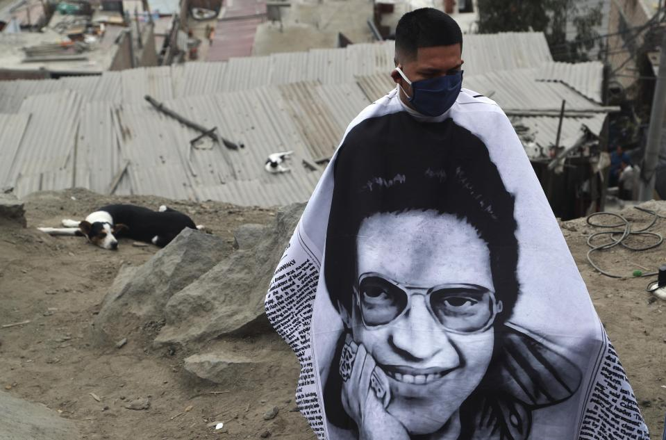 A resident, wearing a barber's apron emblazoned with an image of salsa singer Hector Lavoe, waits to receive a free haircut from Josue Yacahuanca, in the San Juan de Lurigancho poor district of Lima, Peru, Friday, June 19, 2020. Yacahuanca seeks out clients devastated by a quarantine that's gone on for nearly 100 days in an attempt to stem the wave of new coronavirus infections. (AP Photo/Martin Mejia)