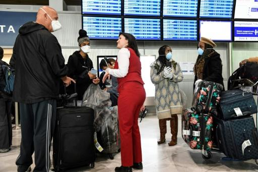 Passengers wearing masks speak with a staff member at Paris-Charles-de-Gaulle airport in France, after the US president announced a shock 30-day ban on travel from mainland Europe to the US