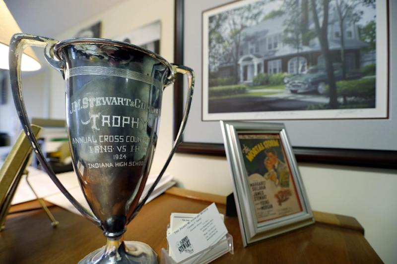 In this photo made on Friday, Dec. 20, 2013, a trophy that was awarded by the hardware store that the father of Hollywood legend Jimmy Stewart owned, sits on the desk of Timothy Harley, executive director of the Jimmy Stewart Museum, in front of a portrait of the house where Stewart grew up, in Indiana, Pa. (AP Photo/Keith Srakocic)