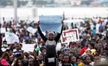 A demonstrator holds a sign during protest over alleged police brutality in Lagos