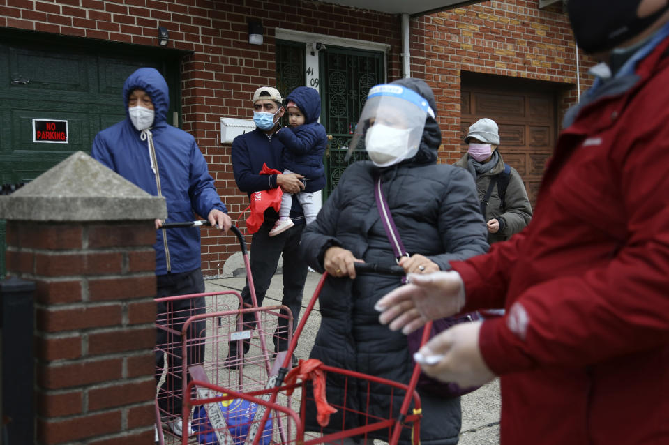 Antonio Sanchez, second from left, holds his 2-year-old daughter, Kyle, as they wait in line for food at the United Sherpa Association's weekly food pantry on Friday, Jan. 15, 2021, in the Queens borough of New York. The pantry began in April with a focus on the Nepalese community, international students and families living in the country without permission. (AP Photo/Jessie Wardarski)