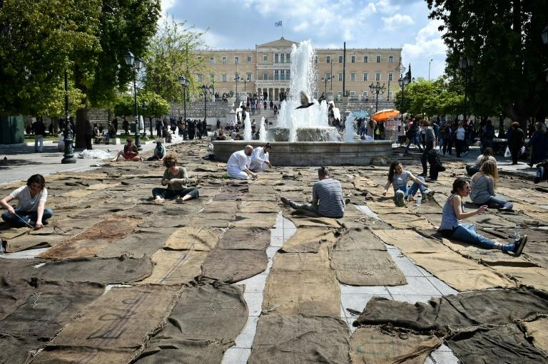 "People sew jute sacks during a performance of ""Check Point - Prosfygika"" by Ghanian artist Ibrahim Mahama, on Syntagma square in Athens on April 7, 2017 on the eve of the opening of the 14th edition of the Documenta 14 art exhibition"