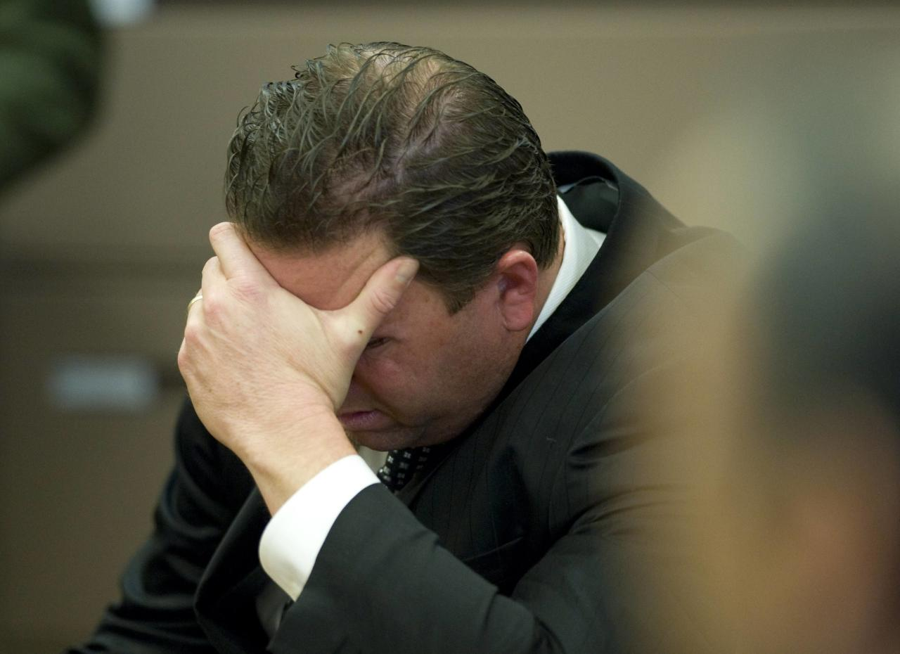 Former Fullerton police officer Jay Cicinelli puts his head in his hands immediately after hearing the not guilty verdict in the Kelly Thomas murder trial in Santa Ana, California January 13, 2014. Ex-Fullerton police officers Manuel Ramos and Jay Cicinelli were acquitted on Monday in the 2011 beating and stun-gun death of a mentally ill California homeless man that touched off street protests and political upheaval in the Los Angeles suburb of Fullerton. REUTERS/Mindy Schauer/Pool (UNITED STATES - Tags: CRIME LAW)